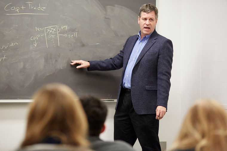 A middle-aged man in a blue blazer in front of a chalk board gesturing