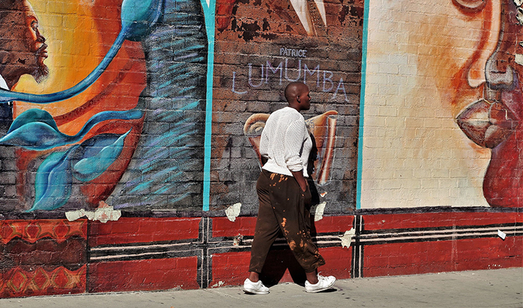 A person walking down the sidewalk next to a wall painted with a mural