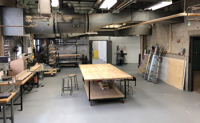 Unoccupied studio space with table in center and supplies and smaller work tables on the sides.