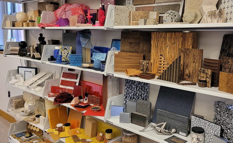 Shelves full of wood and stone tiles, paint jars, and acrylic sheets in a rainbow of colors
