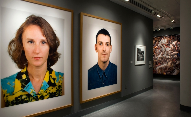 Gallery display of photographs. Most notable pieces are large portraits of a woman and a man.