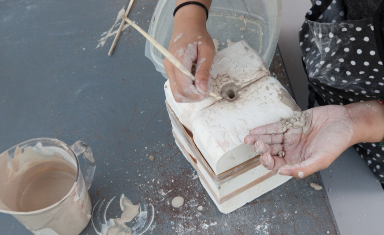Close up of student working with clay using a press mold.