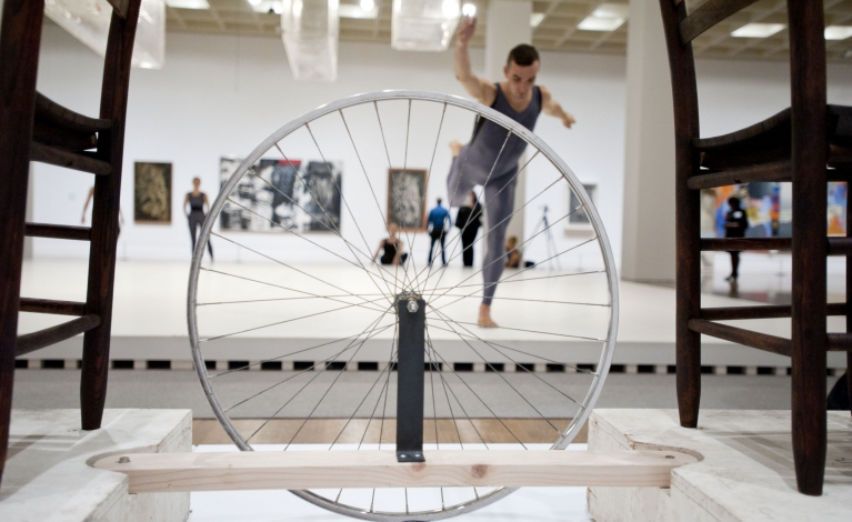 Foreground: sculpture with bicycle wheel suspended between two chairs. Background, performers dancing