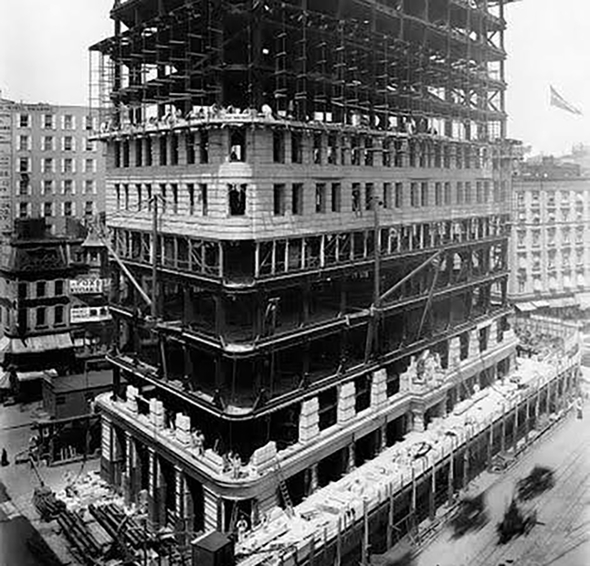 Historic photo of a large building with stone facade under construction