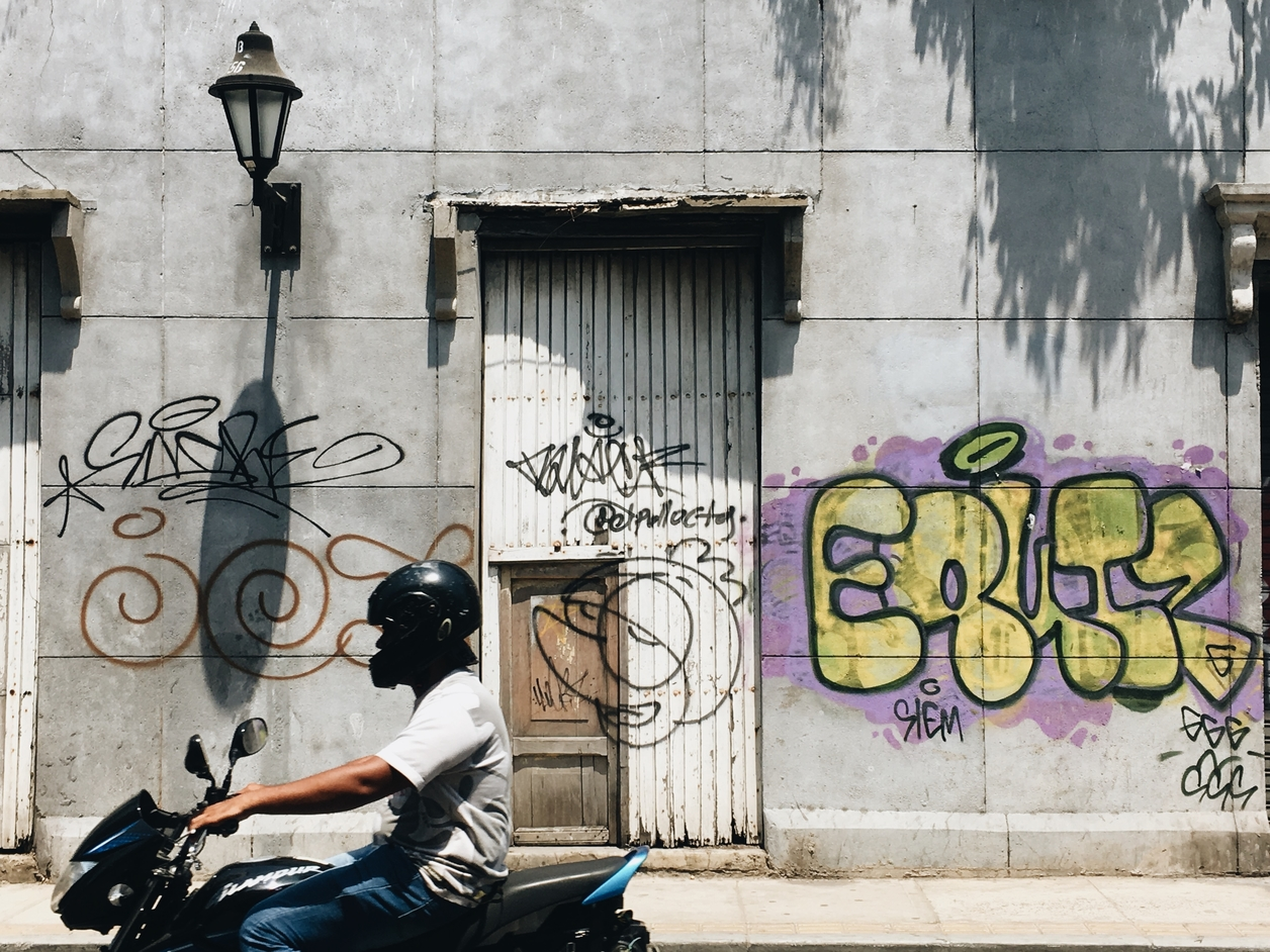 Man riding a motorcycle past a building with graffiti