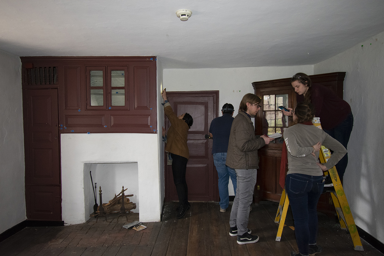 Room of historic house with several students examining it
