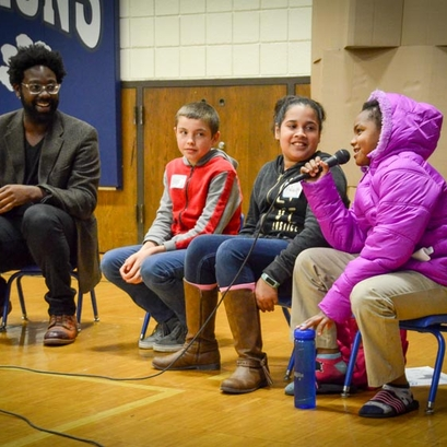 man sitting beside three young children holding a microphone